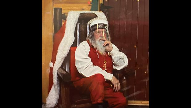SANTA SOCIAL DISTANCES—While working as a professional Santa Claus in Anchorage, Nome's Santa a.k.a. Paul Kudla must wear a face shield and sit behind a glass wall.