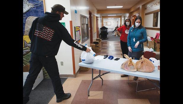 HOMEWORK – Russell Rowe picks up a bag of homework prepared by Nome Elementary School for students. Watching are Nancy Bahnke, left, and NES Principal Elizabeth Korenek-Johnson.