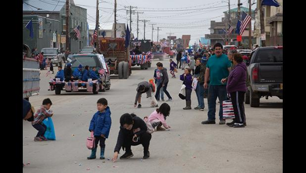 PARADE SCRAMBLE— Kids grabbed at the candy tossed from vehicles as the Nome Fourth of July parade made its way down Front Street Saturday.