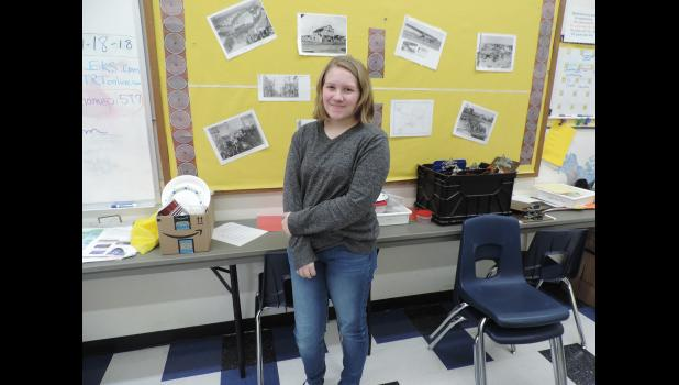 """RECORDING HISTORY - Jenae Matson stands in Colleen Johnson's classroom at Anvil City Science Academy. Students in Mrs. Johnson's Social Studies class completed a project recording interviews with community members recalling important events or topics in Nome's history. Matson interviewed her father, Tony Matson, regarding the """"Friendship Flight"""" of 1988 when Alaska Airlines flew to Provideniya, Russia."""