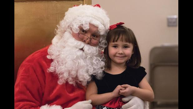 WISH LIST— Santa made a guest appearance at the 20th Annual Christmas Extravaganza on Dec. 7, where Kaiya Theonnes offered valuable gift suggestions.