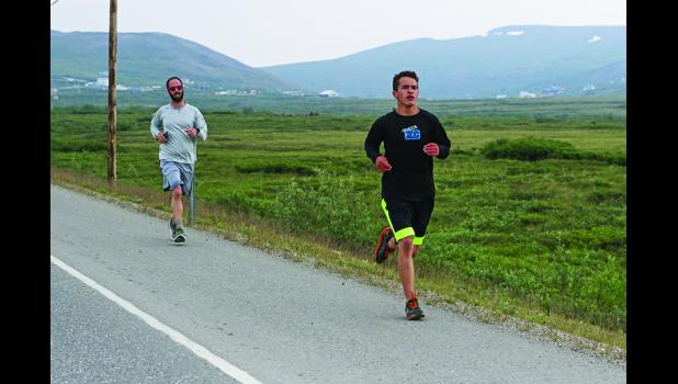 PASSING BY— Aaron Rose, right, overtakes Bryant Hammond on the second leg of the Stroke'n Croak triathlon, held last Sunday in Nome.