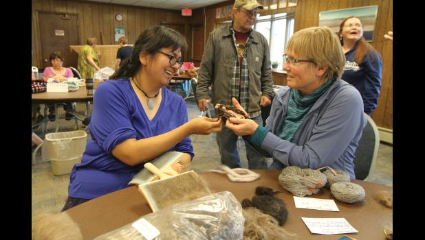 Eve Ulimaugauraq Mendenhall, left, admires a yarn shown by Kate Wattum of Coyote Trail Farm and Fiber Mill