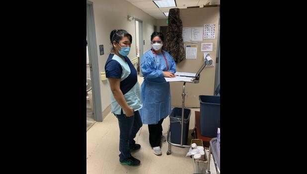 ON THE FRONT LINES— Dr. Cristina Peñon, right, consults with CHA-II Camille Katcheak, left, before donning full personal protective equipment to interview a positive COVID-19 patient in Stebbins.