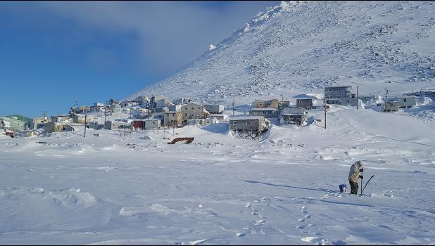 LITTLE DIOMEDE— A Little Diomede man fishes through the ice in this February 2019 photo. The community of Little Diomede is shown in the background, built on the steep slopes of the island located in the middle of the Bering Strait.