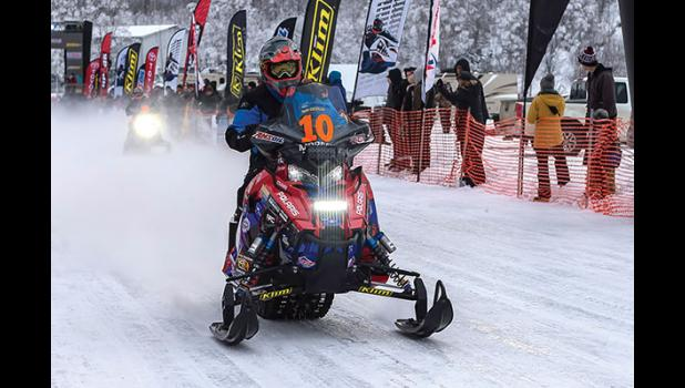 IRON DOGS— Iron Dog rider Mike Morgan roars out the gate with team mate Chris Olds following, on Sunday, Feb. 18 as the Iron Dog snowmobile race started in Big Lake