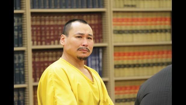 SENTENCED— Gilbert Olanna was sentenced to 75 years in prison for the murder of his girlfriend Esther Lincoln, in Nome's courthouse on Tuesday, January 10. For most of the time during the sentencing he sat slumped over the table but during one of the proceeding's breaks he looks towards the Lincoln family present at the sentencing.