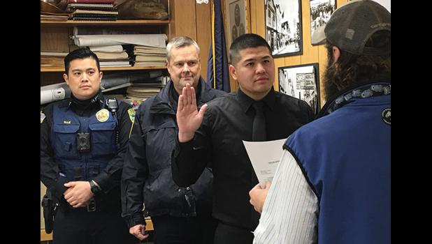 New NPD officer Vingent Nguyen is sworn in by City Clerk Bryant Hammond as NPD Chief Bob Estes and officer Alex Le look on.