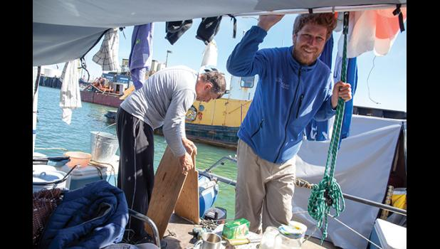ON BOARD— Alexander Lomb, left, works on a splash guard for their remaining Mercury outboard motor while Anatoli Kazakevich visits with the Nugget reporter. The Russians traveled from Lake Baikal to Nome in a catamaran and are currently en route to Dutch Harbor and on to Anchorage, their ultimate destination.