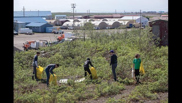 CLEANUP – Lisa Leeper, right, and her crew of clean uppers pick up trash across the Teller Road from Nome-Beltz High School Saturday.