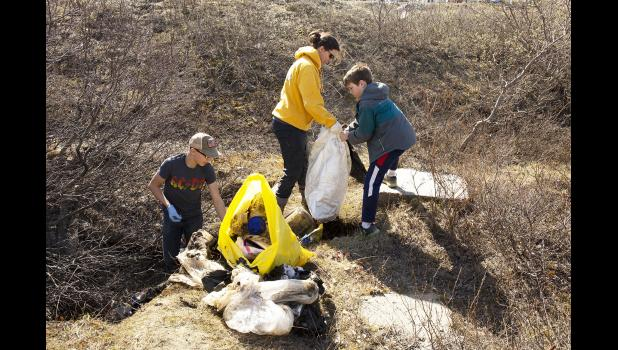 SPRING CLEANUP— Reese Bahnke, left, pulls trash out of a ditch near the Nome-Teller Highway while Hayden Leeper helps Nancy Bahnke fill a trash bag Saturday during the annual Nome spring cleanup.