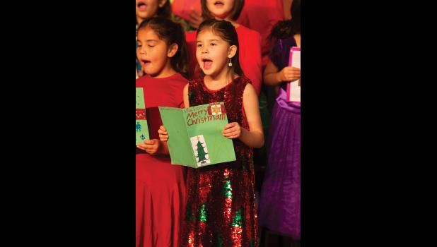 SING IT! – Second graders Hannah Harrelson and Violet Fagundes add their voices to Christmas Card during last week's Nome Elementary Holiday Program.