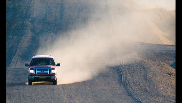 RAISING DUST – A pickup truck on Greg Kruschek Avenue raises a cloud of dust. With no snow yet Nome is a dusty place.