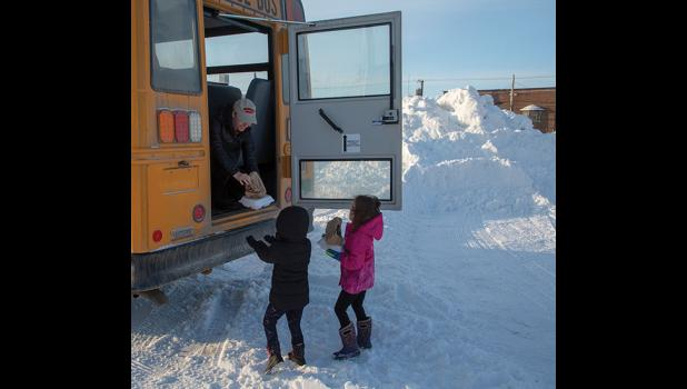 CHOW BUS— A Nome Public Schools bus stops on First Avenue to deliver breakfast and lunch to young students.