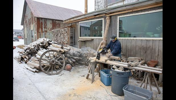 TO NOME BY CANOE – Jerry Pushcar works on driftwood he has gathered, cutting it down to size for his woodpile. Pushcar made his home in Nome after having arrived here 42 years ago by canoe.