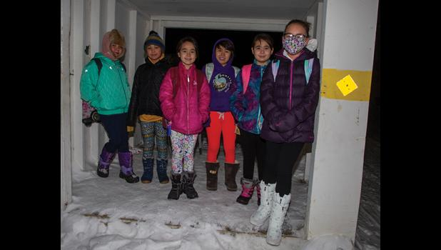 STATUS GREEN – Nome's students headed back to school Monday as the number of Covid-19 cases declined significantly. This group of elementary school students was waiting for the bus at the 3rd Ave and Bering Street bus stop.