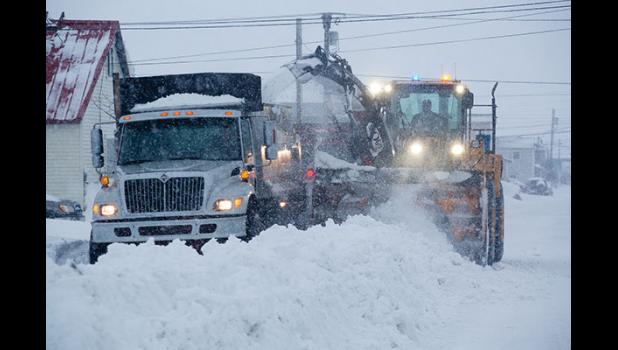 DIGGING OUT— After a series of snow storms, city workers are busy plowing roads.