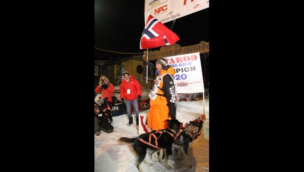 Thomas Waerner waving the Norwegian flag at the finish line.